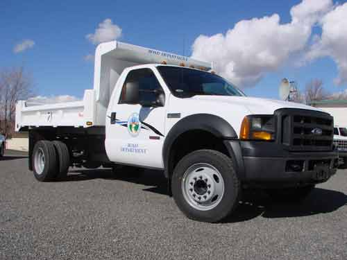 A white ford work truck with a public works logo o